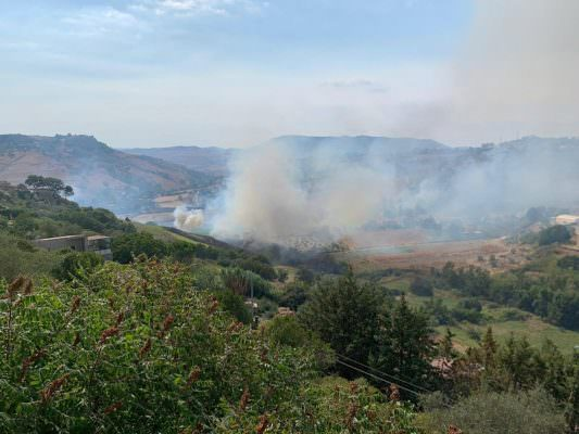 Vasto incendio minaccia le abitazioni di un rione nel Catanese: operazioni di spegnimento in corso