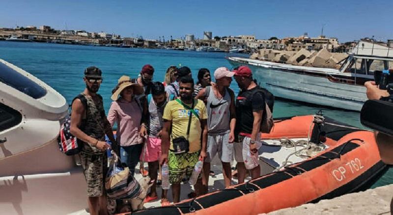 """Occhiali da sole, cappelli e barboncino al guinzaglio. Sbarco """"singolare"""" a Lampedusa: migranti-vacanzieri"""